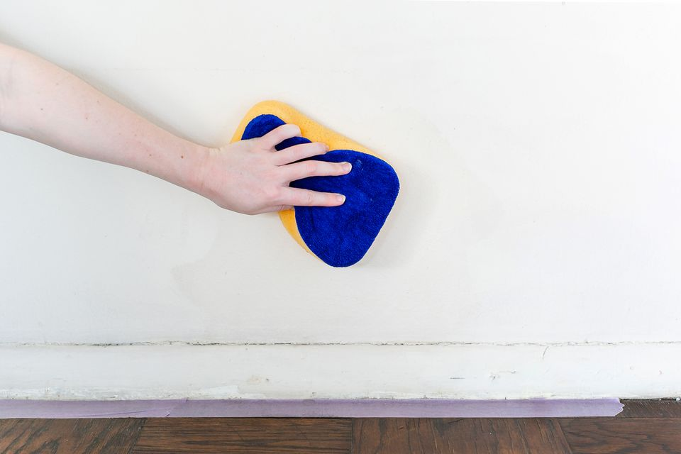 wiping walls down with a sponge