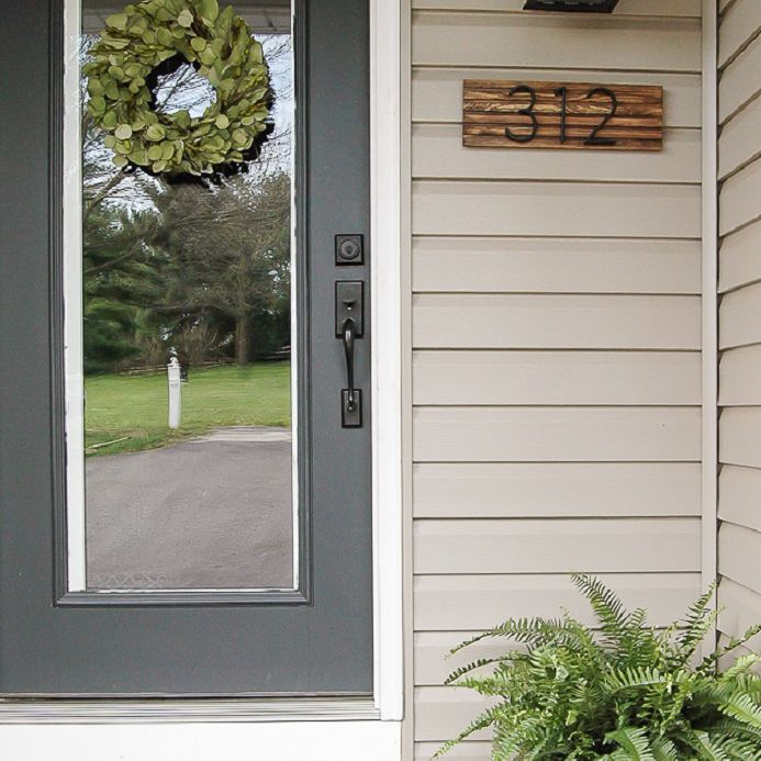 A modern wooden DIY number sign next to the front door.