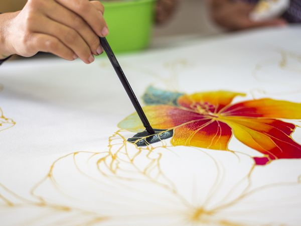 Hands painting a flower design on fabric.