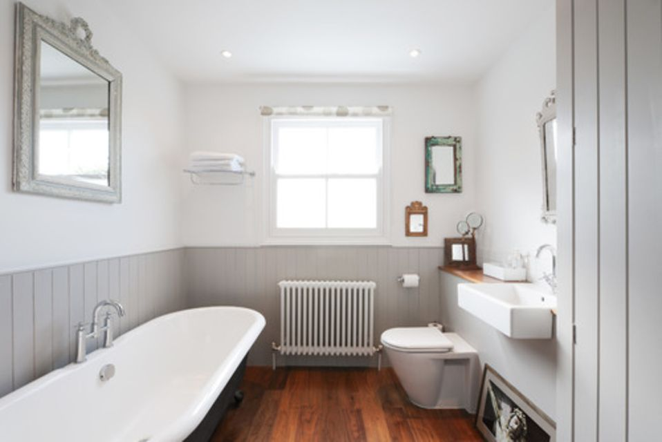Grey and white bathroom with tub, toilet, and radiator.