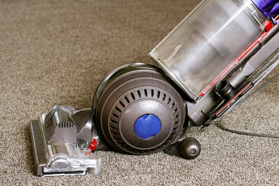 Vacuum cleaner with HEPA filter passing over tan carpet