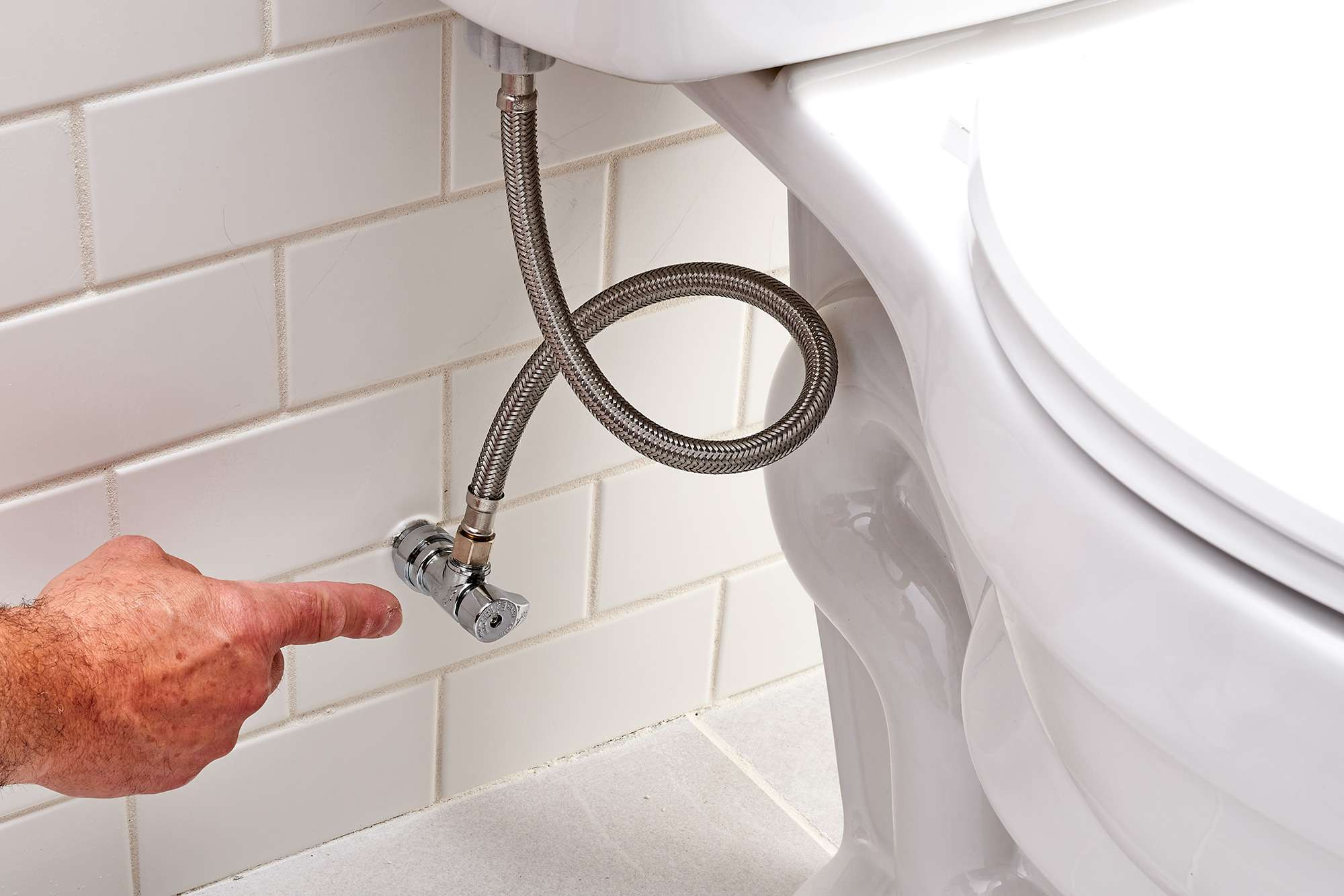 Shutoff valve pointed out underneath toilet