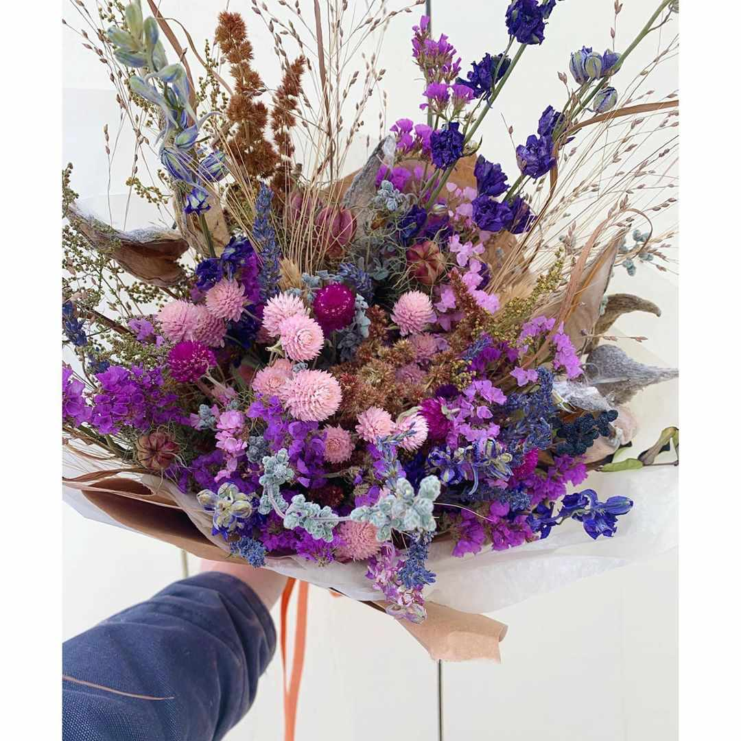 Hand holding bouquet of purple and violet flowers