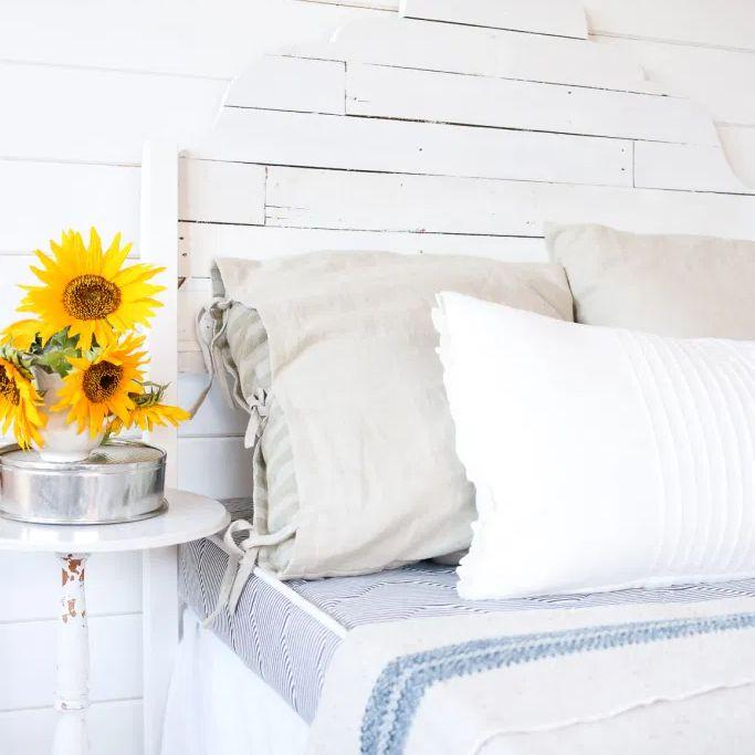 A white pallet headboard in a bedroom