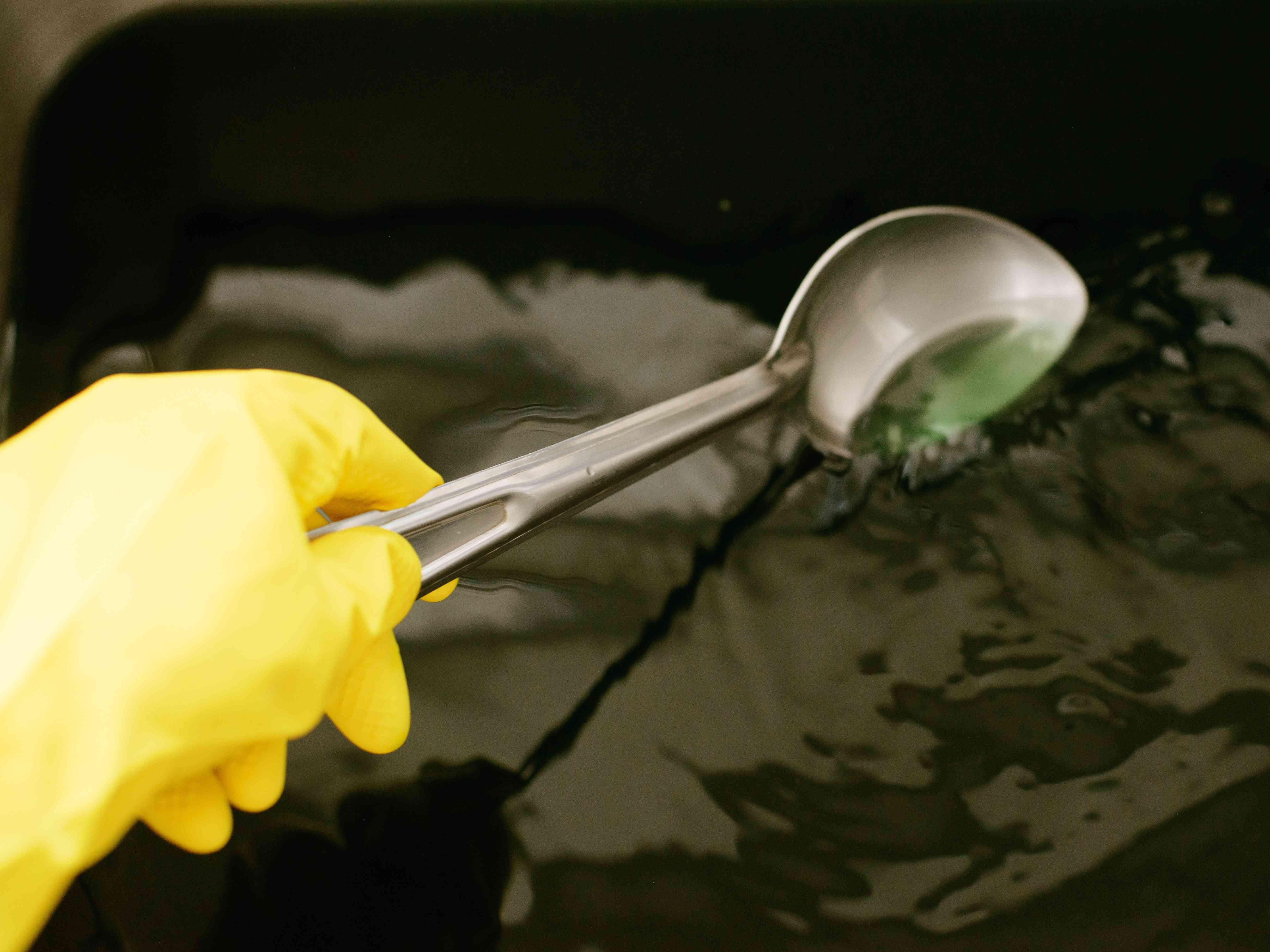Metal spoon mixing fabric dye in sink