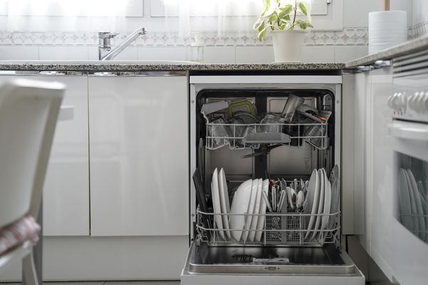 A loaded dishwasher in a moden white kitchen