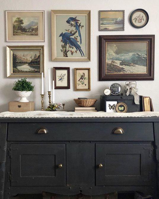 Black dresser with antique prints above it