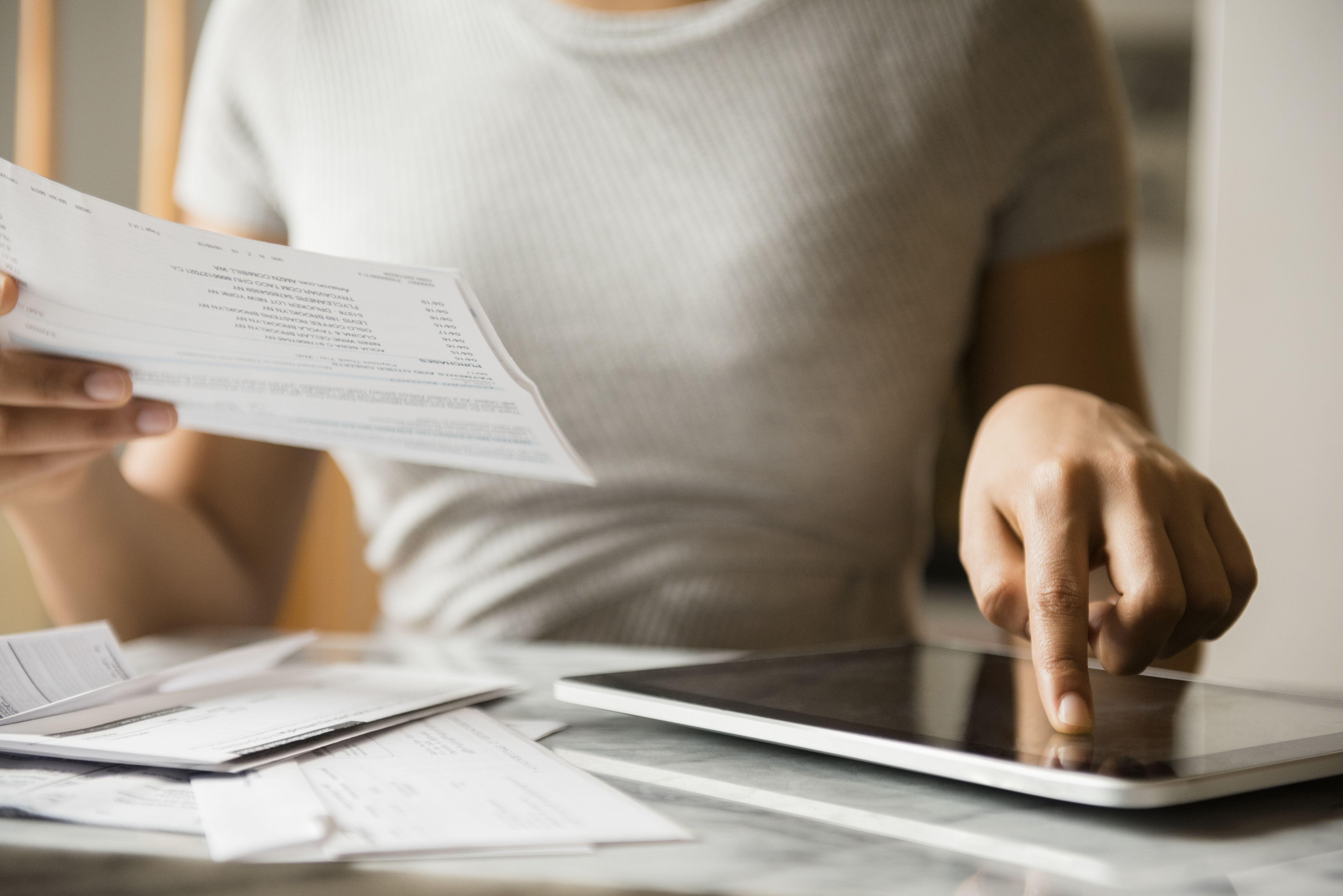 Mujer afroamericana que paga facturas con tableta digital