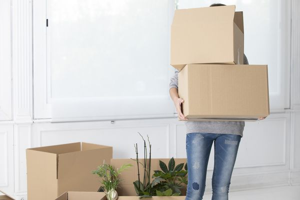 Unrecognizable woman carrying cardboard boxes in new home