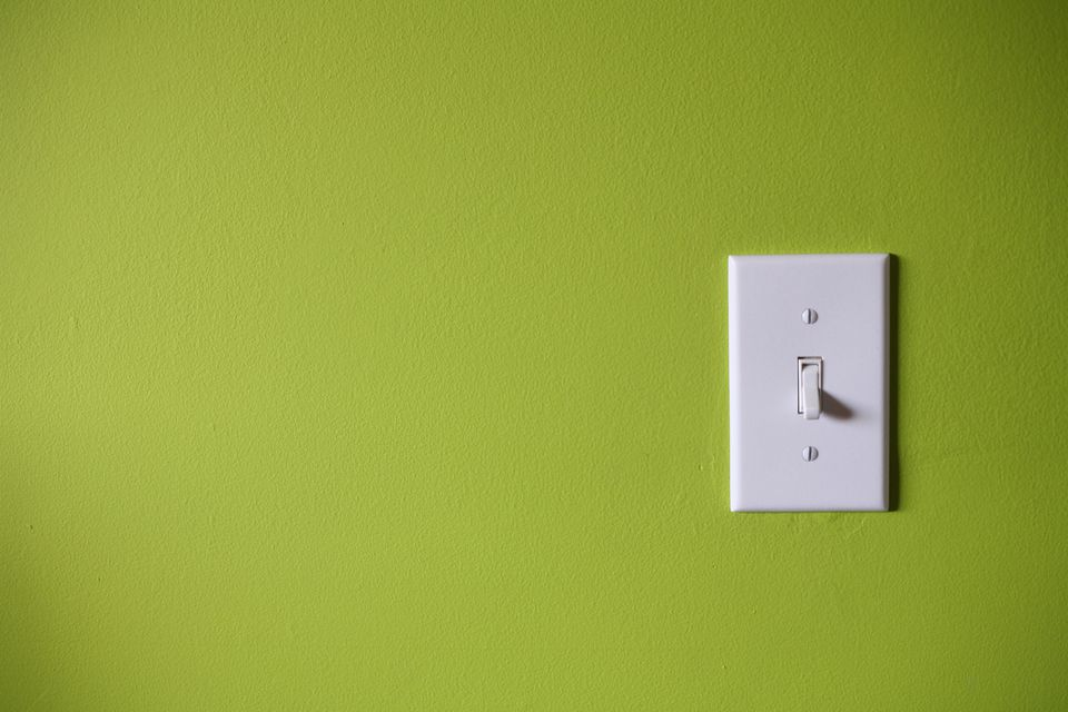 Symptoms of a defective wall switch light switch in front of green background aloadofball