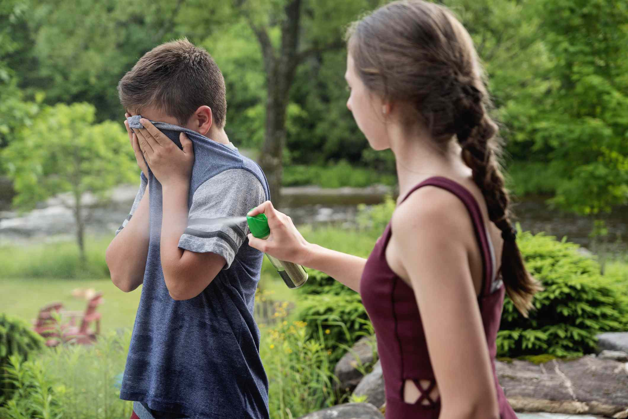 Girl spraying boy with bug repellent.