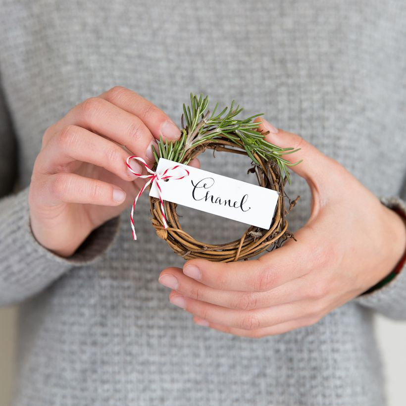 Woman holding a miniature wreath placecard.