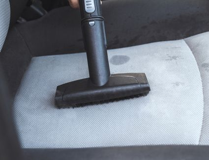 person vacuuming an upholstered car seat