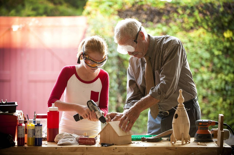 Grandfather helping granddaughter build birdhouse in garage