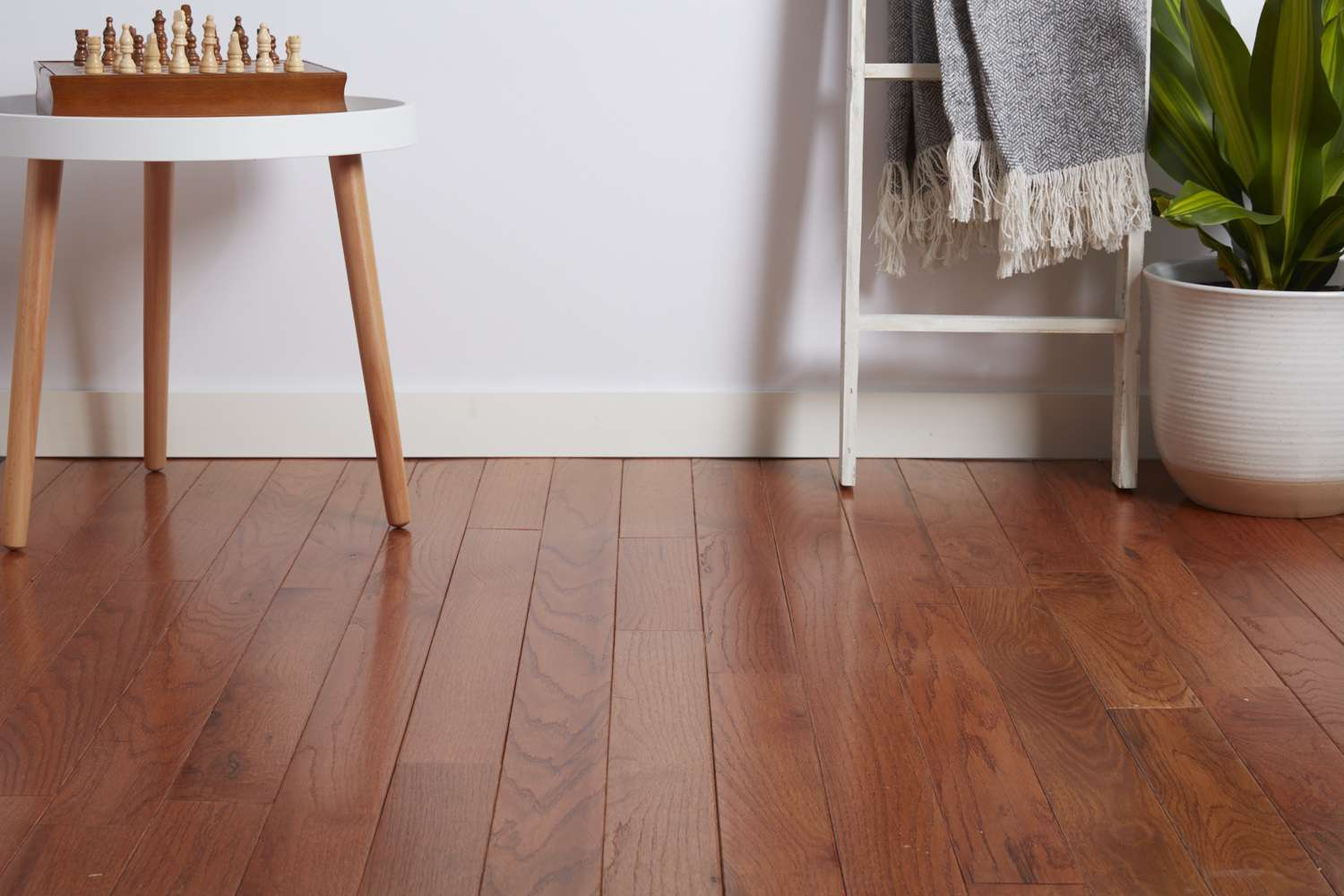 Hardwood flooring with side table and chess set by houseplant