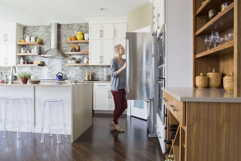 Woman opening refrigerator door in kitchen