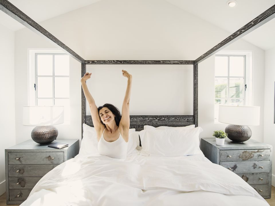 Hispanic woman stretching arms in bed