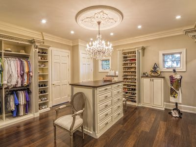 Custom closet with island and chandelier light hanging from the ceiling.