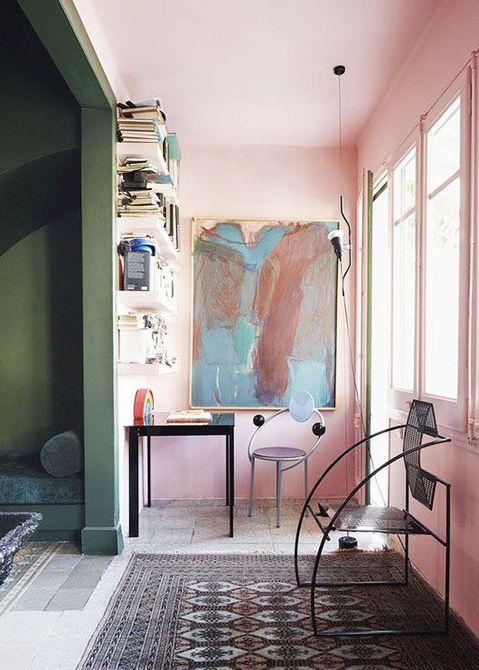 Oficina en el hogar con decoración global con paredes de color rosa y grandes obras de arte