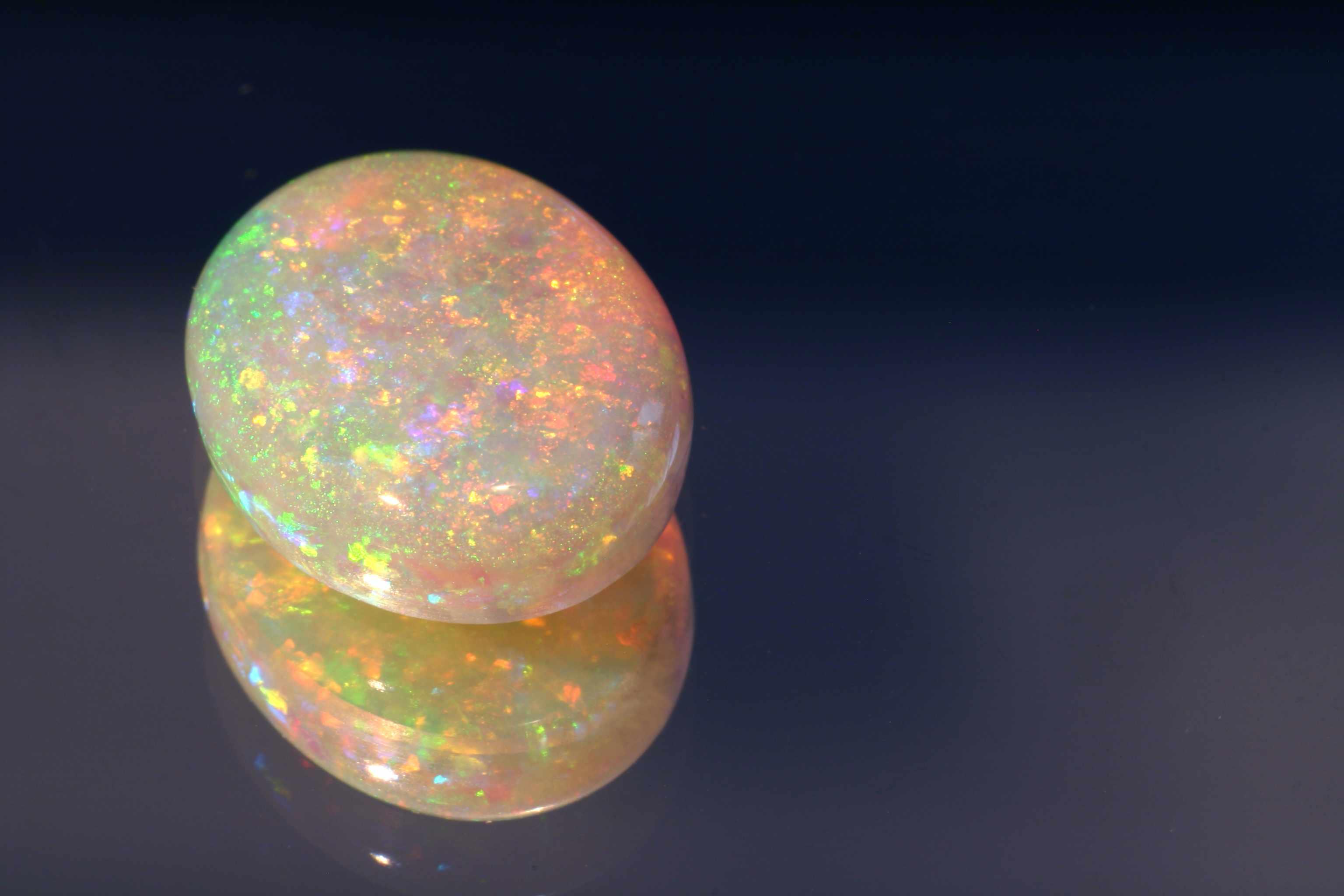 polished opal gemstone on a dark background