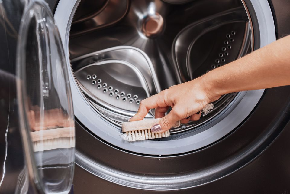 person scrubbing the inside of a washing machine