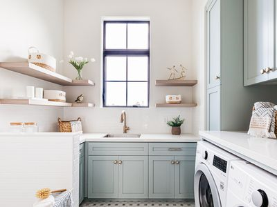 Laundry room with light blue cabinets and light wood shelves with decor throughout