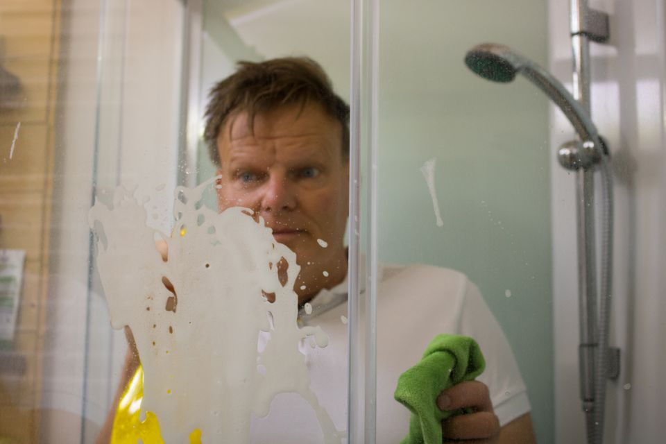 man cleaning glass in shower