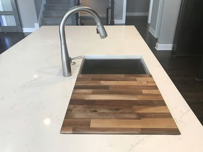 Butcher block cutting board next to sink in marble countertop