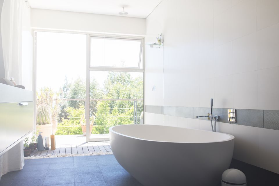 Modern bathroom with large white bathtub and patio door