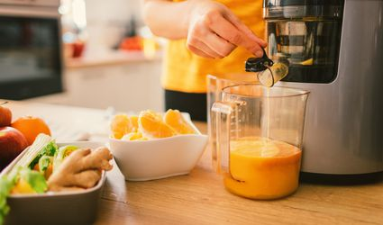 Woman in yellow shirt using a cold press juicer with oranges, celery, and ginger