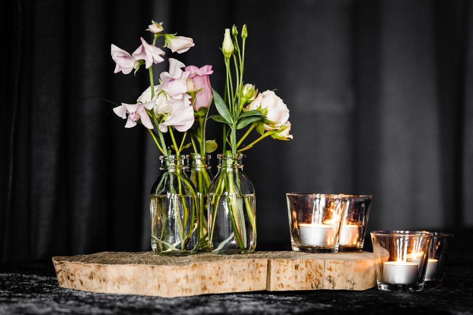 Small vases of flowers on a table with votive candles