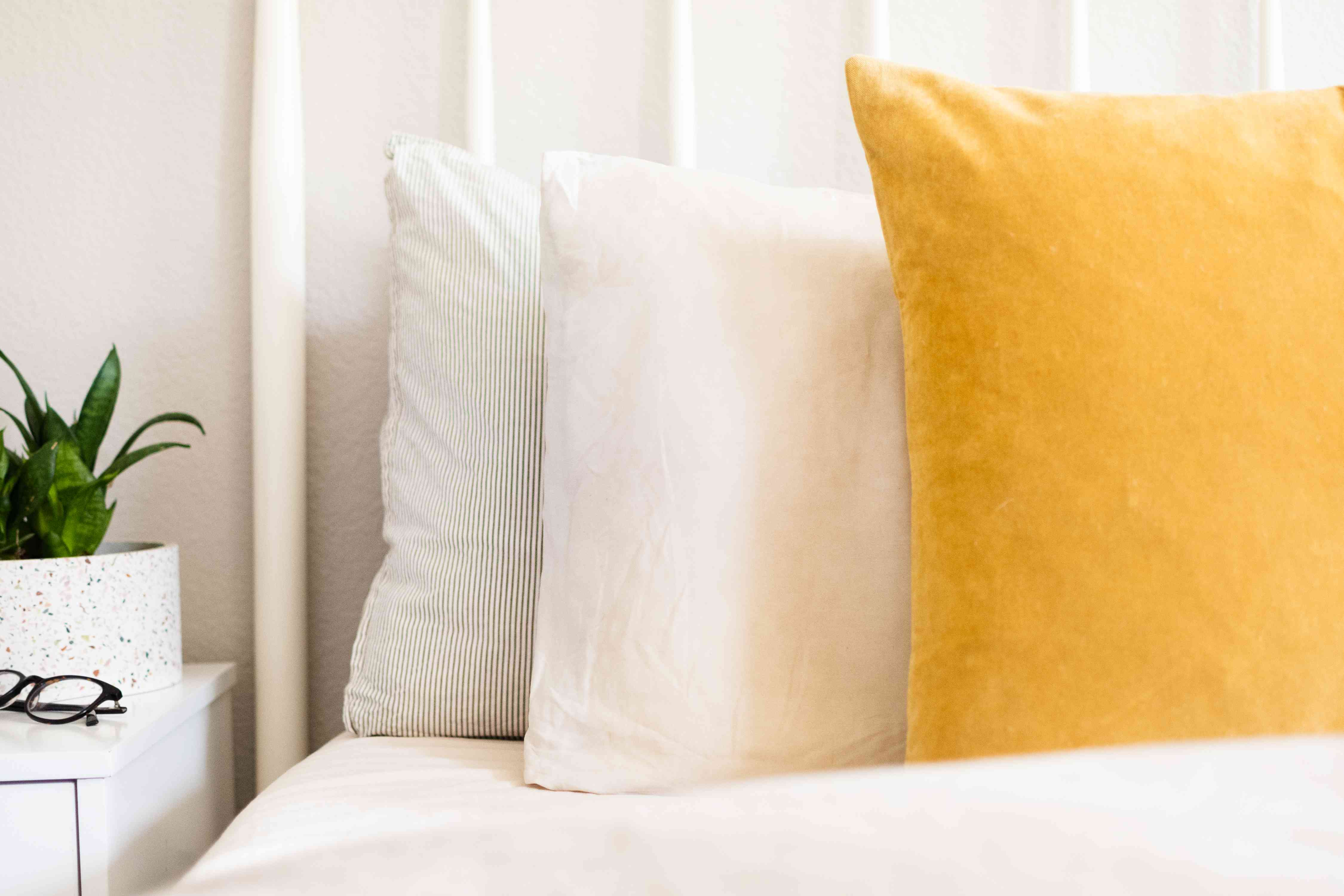 White and yellow pillows on bed closeup