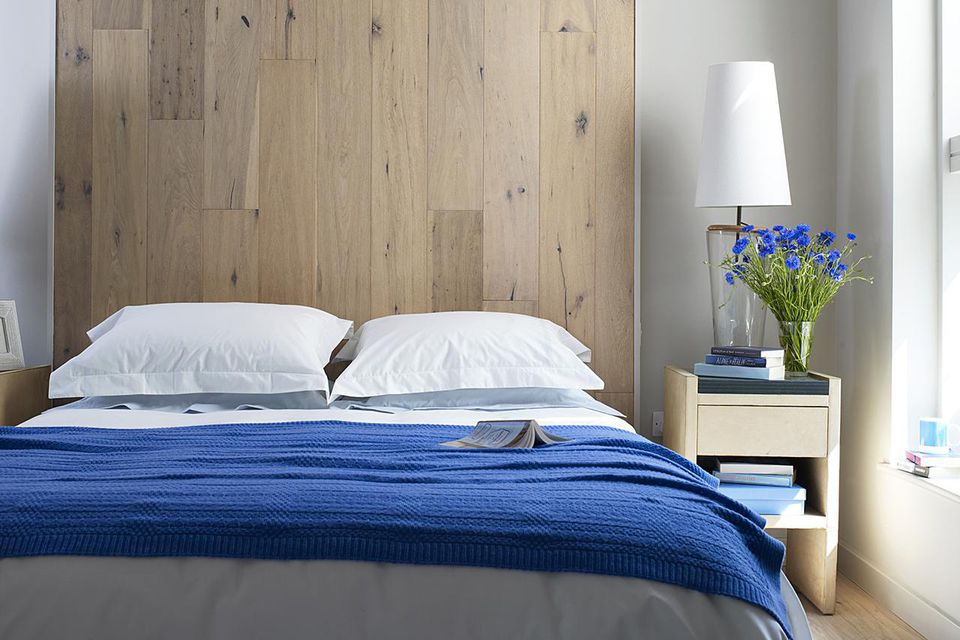 Open book on bed with white pillow cases, blue bedspread, large wooden headboard, and vase of blue flowers and electric lamp on bedside table in brightly lit bedroom