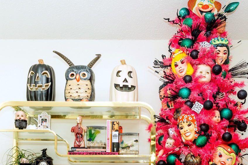 Árbol de Navidad flaco decorado en blanco y turquesa .Árbol de Navidad rosado orientado hacia Halloween con máscaras y adornos negros