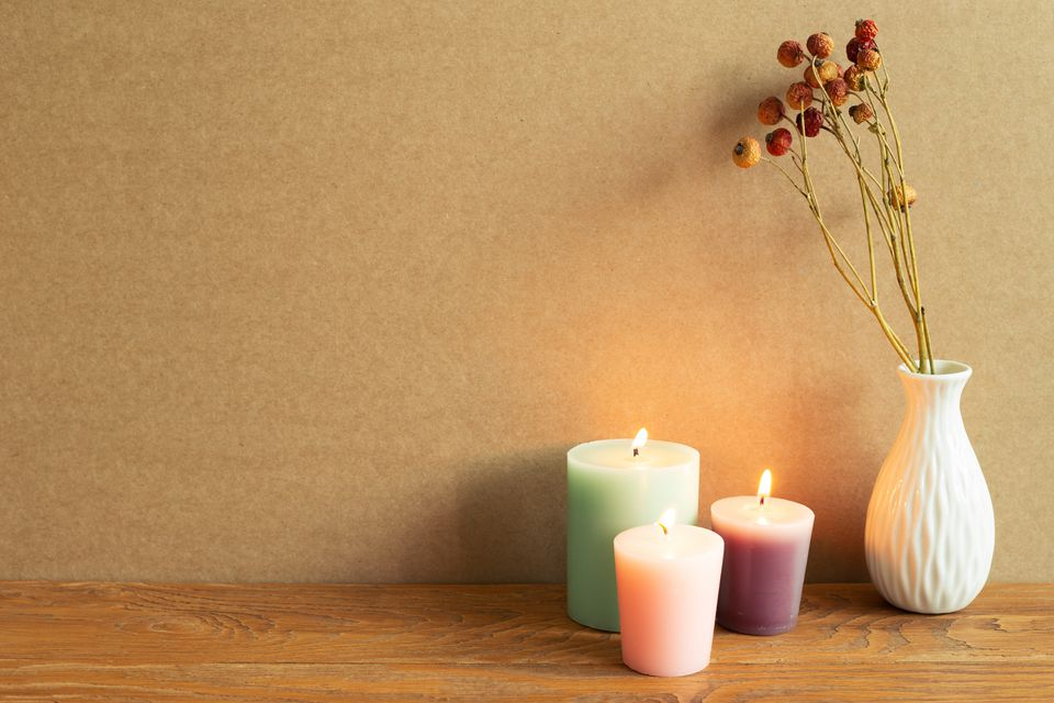 Lit pastel candles and vase with flowers on wood table next to tan wall