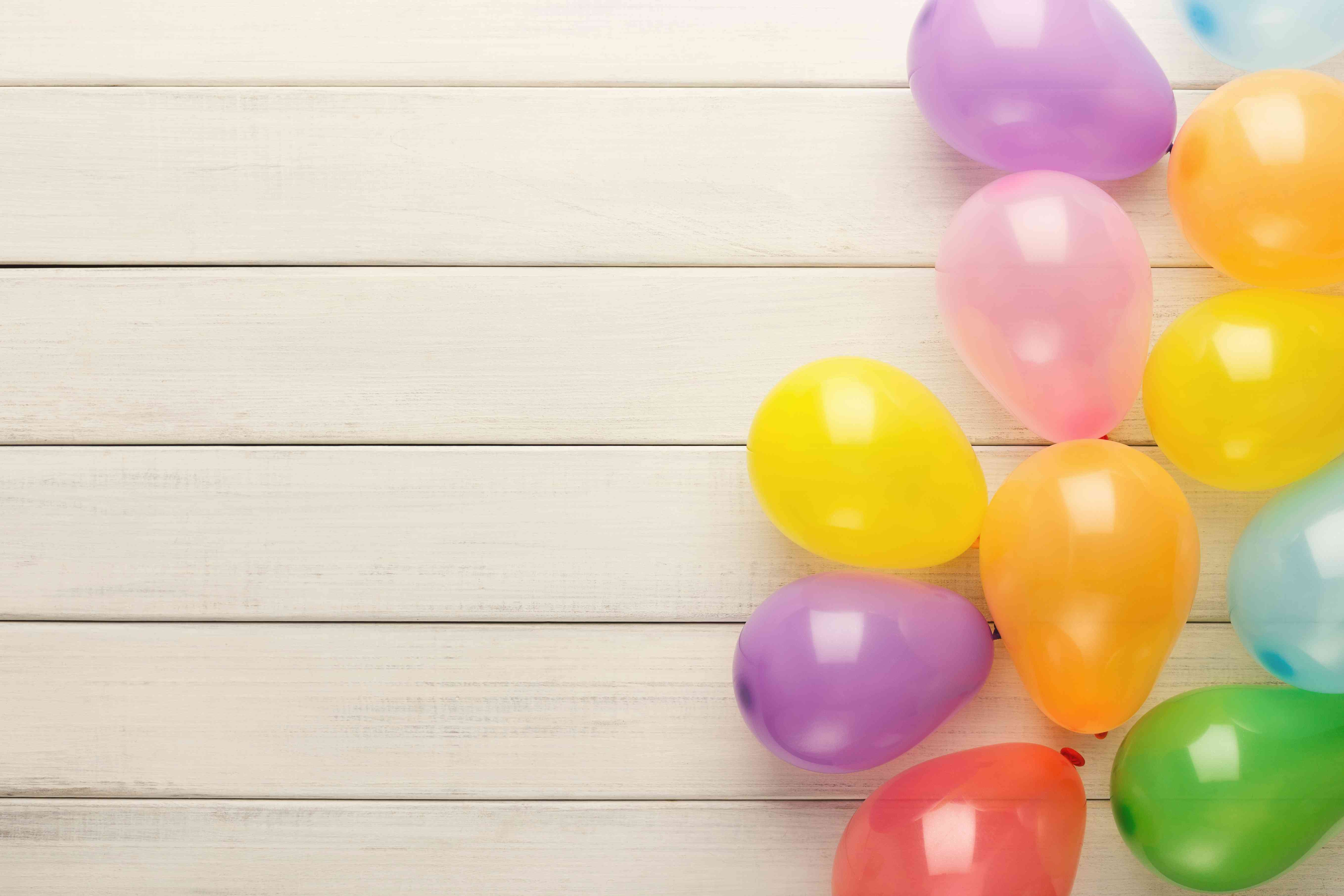 Colorful balloons on white rustic wood, birthday background, top view