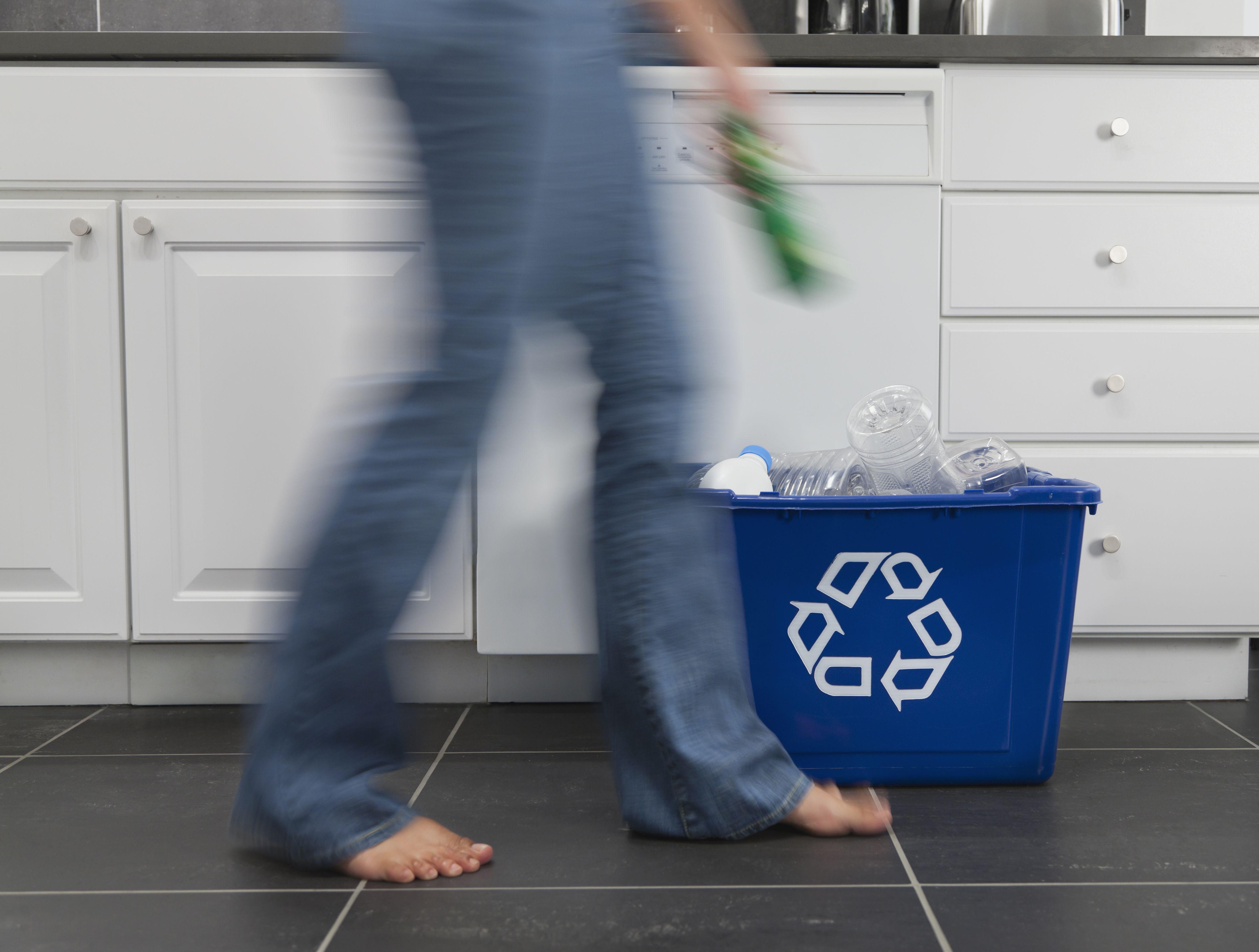 Hispanic Woman Putting Plastic Bottle In Recycling Bin