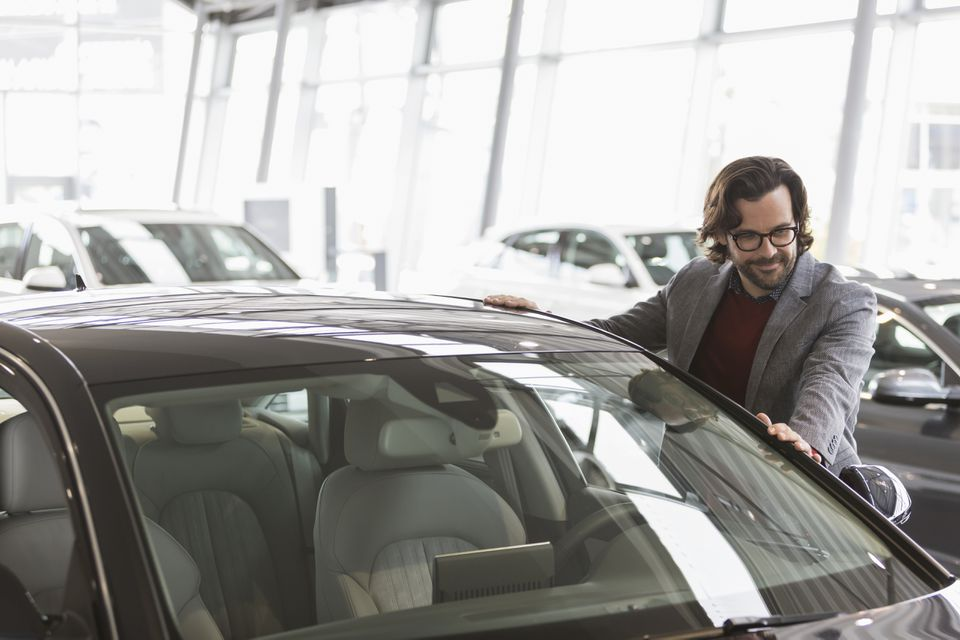Male customer eyeing new car in car dealership showroom