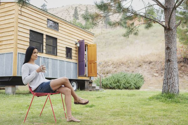 Young woman sitting outside her tiny house