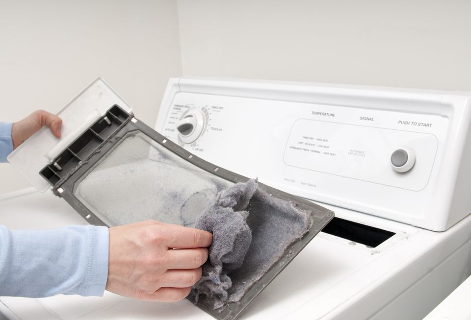 Man cleaning lint trap on dryer