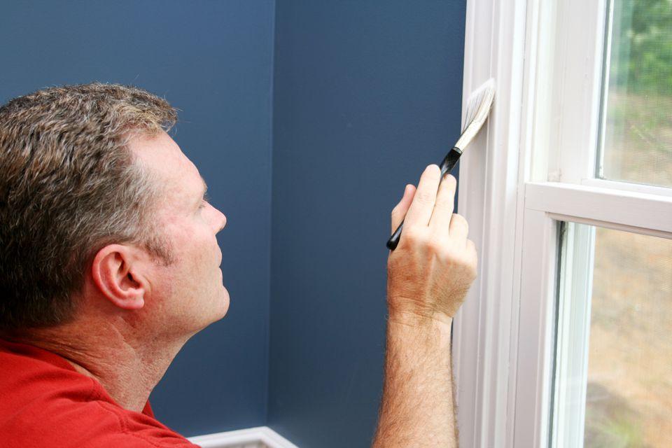 Man painting window trim