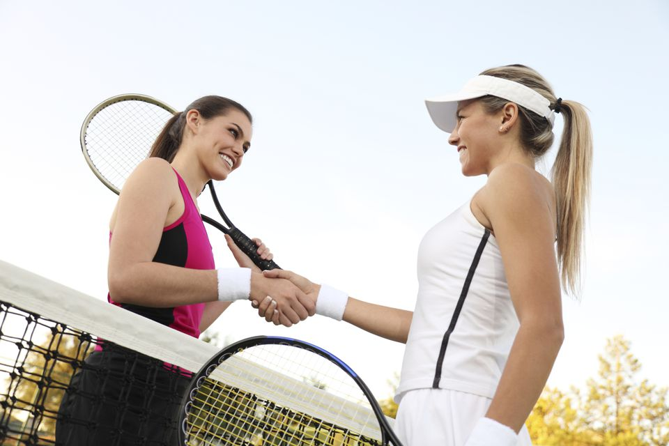 Winner and loser shaking hands after a tennis match
