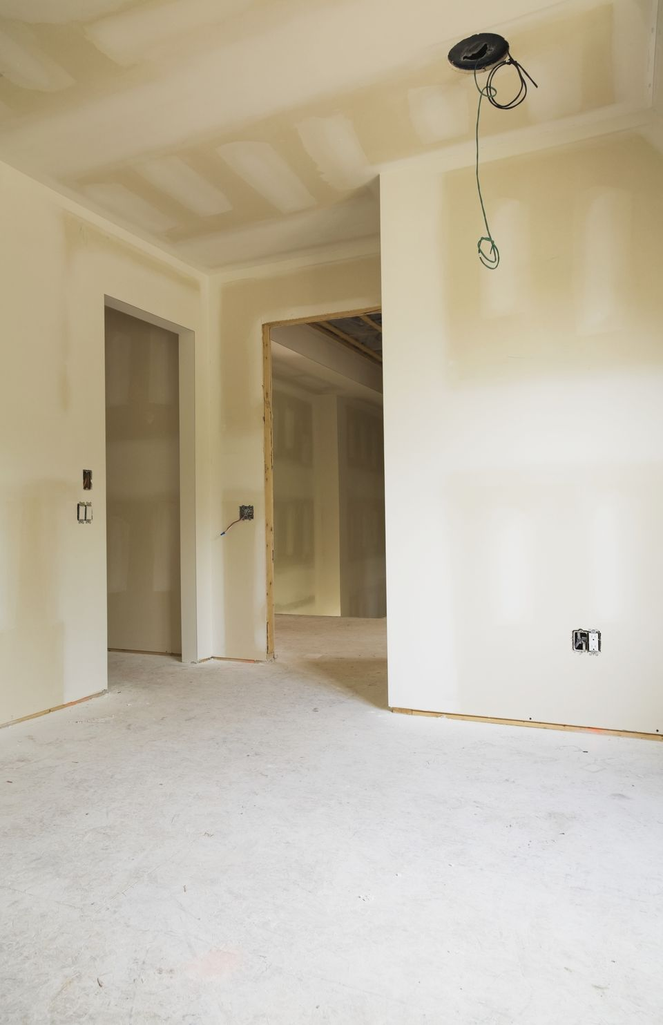 An unfinished room with hung drywall