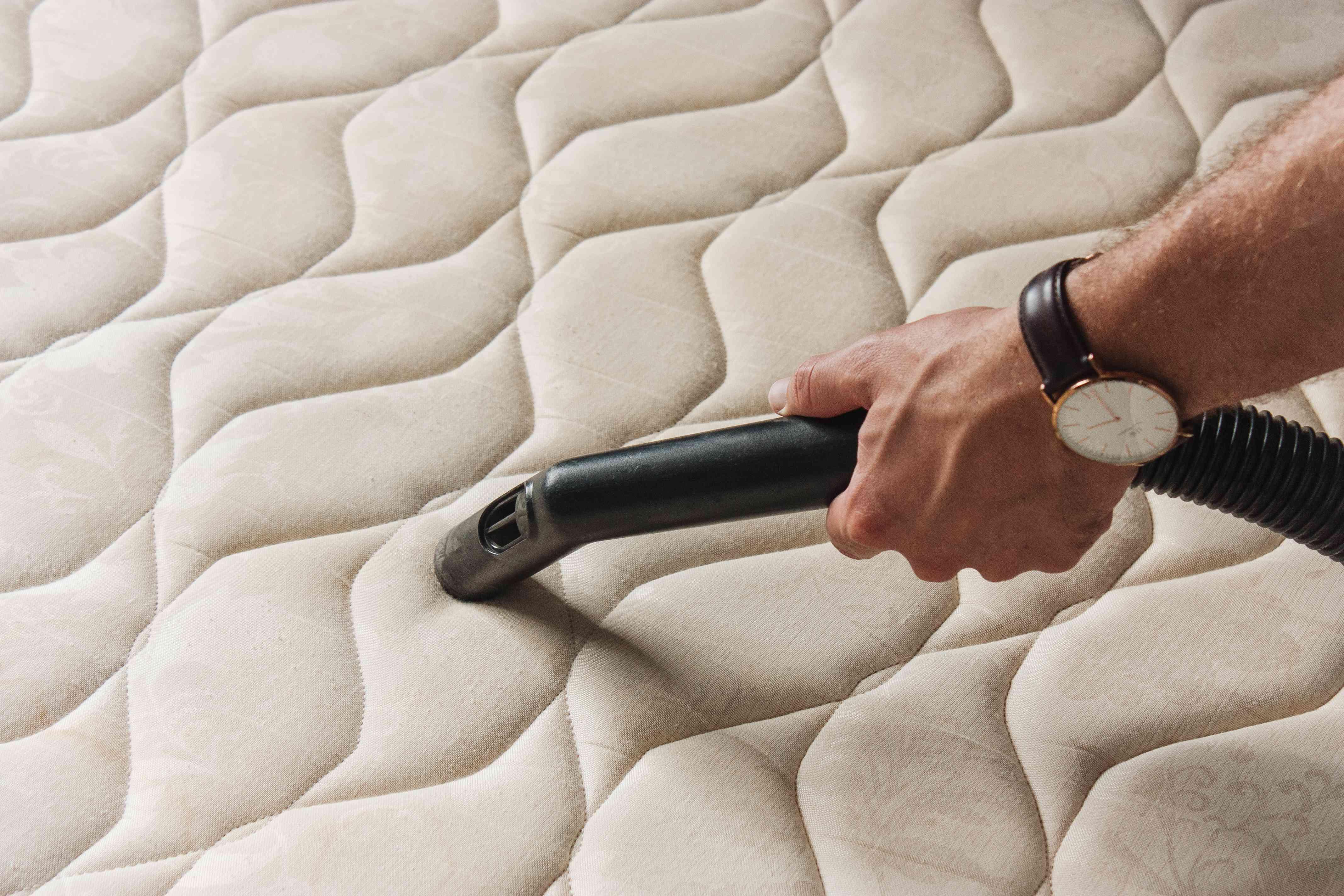 person vacuuming a mattress