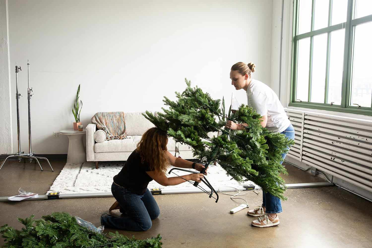 assembling an artificial christmas tree with two people
