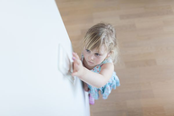Young girl using light switch
