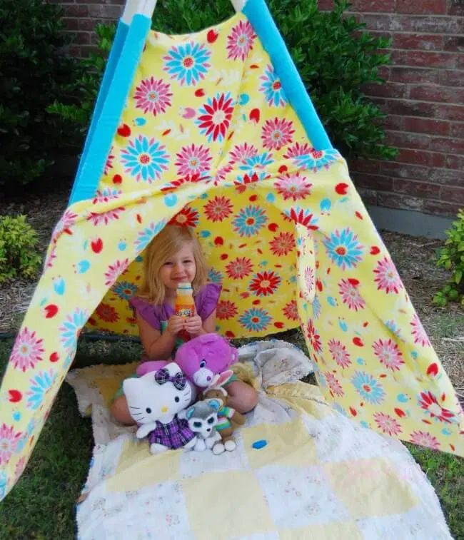 A girl sitting in a tent with flowers all over it
