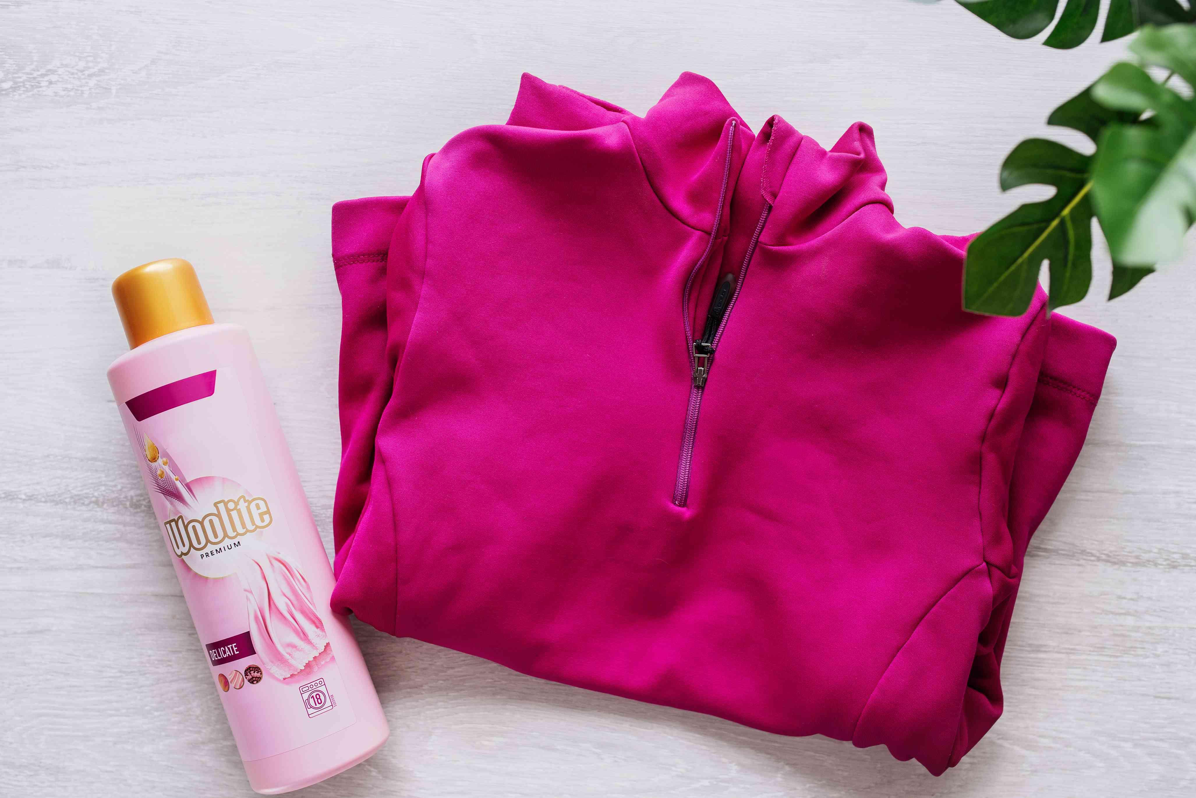 Pink fleece jacket folded next to pink bottle of Woolite mild detergent