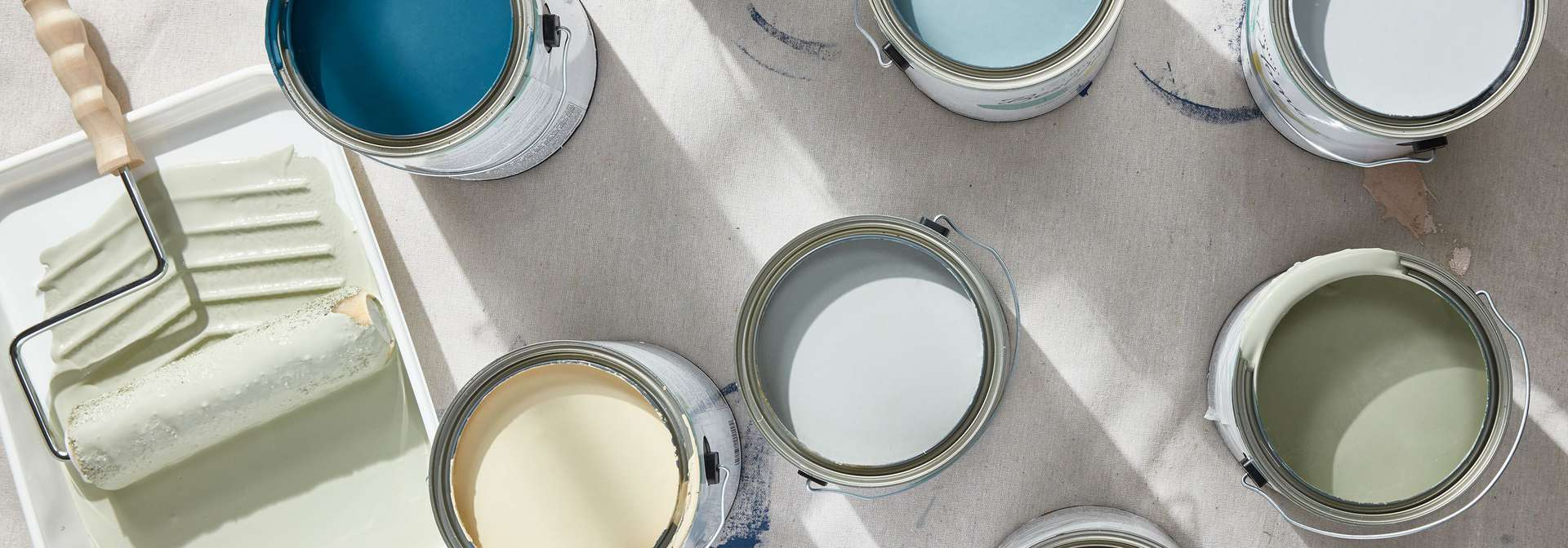 The Spruce best chalky paint colors in cans, laid out on a drop cloth with a paint roller in the corner.