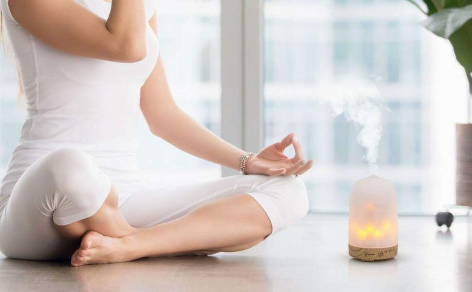 woman meditating next to oil diffuser
